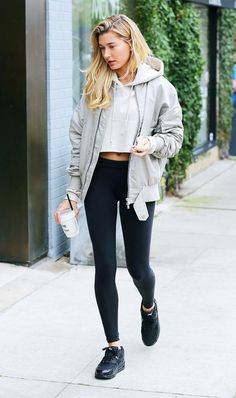 Hailey Baldwin does color blocking right in black sneakers and leggings topped off with a beige cropped hoodie and beige bomber