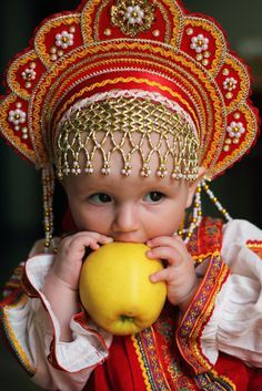 A toddler has Russian kokoshnik on her head and a tasty apple in her hands.