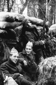 British soldiers in a trench in France make merry with paper hats from Christmas crackers while a sentry uses a mirror to keep watch on no man's land, 1916.