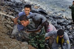 Em 16 de Julho de 2011, dois oleodutos explodiram no porto de Dalian, no nordeste da China. Fotógrafo: Lu Guang.