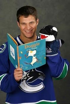 """As the poster of this image where I found it wrote, """"here's Kevin Bieksa attending a remedial reading course instructed by a freakin' sock puppet…"""" The puppet in question is, of course, Canucks mascot Fin. Hockey Teams, Hockey Players, Ice Hockey, Vancouver Canucks, Love My Boys, My Love, Win Or Lose, World Of Sports, Just For Fun"""