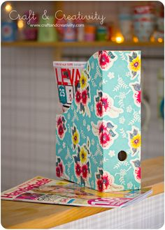 I used scrapbook paper, spray adhesive and a kraft knife to make white cardboard IKEA magazine files into something pretty and color-coordinated to my LR decor.  This tutorial uses decoupage glue and gift wrap on wooden magazine files.