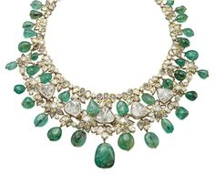 Emerald and diamond necklace by Mouawad. Designed as a line of table-cut diamond collet clusters interspersed by brilliant-cut diamonds with emerald beads, and suspending at the front a row of larger table-cut diamonds alternated with diamond-set flowers, to the fringe of emerald beads, 42 cm long. Signed Mouawad.