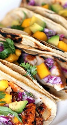 grilled chili lime fish tacos with sour cream cabbage slaw, avocado, and mango