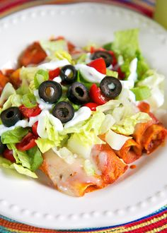 Taquito-lada Casserole Recipe - use frozen Jose Ole taquitos for a quick Mexican taquito enchilada casserole. Only three ingredients! Top with lettuce, tomatoes, olives, green onions and sour cream.