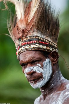 An Asmat warrior in a beaded and feathered headdress. Tribe members gave the photographer permission to document their way of life