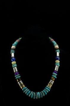 "Tommy Singer Tiger Eye Necklace  Sterling silver and 12K gold filled barrel beads. Genuine Spiny Oyster, Black Onyx, Blue Lapis, Tiger Eye and Coral beads.. Necklace is 20"""" and comes with a certificate of authenticity from the Native American artist.   http://www.sterlingjewelrystores.com/product345.html"