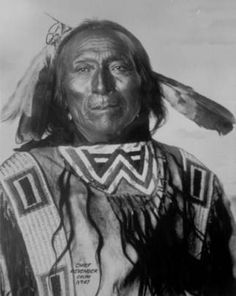 Studio portrait (sitting) of Chief Revenger, a Native American (Crow) man. He wears a shirt with quill-work and ermine fringe, and feather roach.   Photo taken between 1898 - 1900.  Frank A. Rinehart