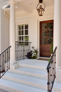 White painted brick + wood door + impeccable pendant lighting | Houzz