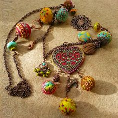 I think the artist uses some felted spheres on which to embellish with embroidery, beads etc.  The site is in French and sadly, I can't read it.