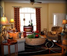 Transitional family room with flame-stitch curtains, large wicker ottoman and curved gray sofa. www.fluffyourstuff.com