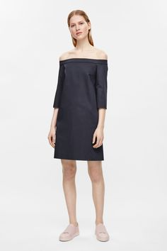 An off the shoulder design with a gathered elastic back, this dress is made from a cotton with a comfortable stretch. A straight fit, it has in-seam pockets, neat finishes and 3/4 sleeves with slits.