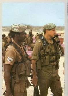 """South African Defense Force 32 Battalion troopers in 1982. They both wear Pattern 83 """"battle jackets"""", """"Transkei"""" elite camo berets, and carry folding-stock Vektor R4 automatic rifles."""