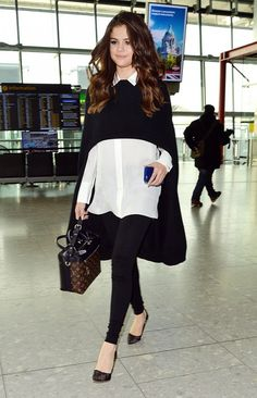 Selena Gomez pairs a black poncho over an Alice + Olivia button down, with Alice + Olivia leggings, a Louis Vuitton bag, and black pumps