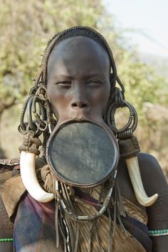 Hundreds of years ago other tribes would kidnap the Murci women and take them back to their villages to be their wives. So the Murci men inserted plates in the women's lips so they would not be attractive to other tribes. Now the lip plates are considered beautiful and the women create and decorate their own plates to be the most beautiful.