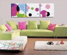 Here is frame of white canvas on the wall and there is round circles on it in neon color and some line circle also pattern on it.