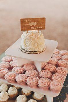 mini wedding cake on top of cupcake tower