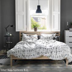 Ein helles Bett aus Kiefer bildet den Mittelpunkt in diesem schlichten Schlafzimmer. Der weiß-grau karierte Fliesenboden und die weiße Muster-Bettwäsche  …