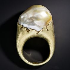 A magnificent custom designed ring by Bali based designer Jean Francois Fichot, hand crafted in 18k yellow gold and featuring an enormous baroque pearl with a golden gray body color, exhibiting spectacular orient. Fichot is a French artist, sculptor, jeweler and gardener who travels the world seeking unusual natural materials from which to create wearable art with a blend of Asian mystery and western elegance. The ring is a size 6 1/2.