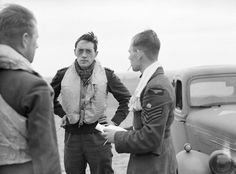 """The strain of battle is beginning to show on the face of acting S/L Brian JE """"Sandy"""" Lane (second left) when huddling with acting F/L Walter J """"Farmer""""' Lawson (far left) and F/Sgt George C """"Grumpy"""" Unwin after return from a sortie to RAF Fowlmere on 21 September 1940. The 23-year-old CO of No 19 Squadron RAF was known to stay calm during tense moments of battle, helping to reassure the pilots under his command."""