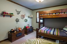We designed this bedroom for 2 young boys who absolutely love animals, who doesn't? The boys needed a place to store their abundance of stuffed animals and custom open top storage bins were the perfect solution. The animal wire heads were a wonderful, fun alternative to art and pulled together the colors from the bedding. We balanced the hardness and weight of the wood in the room with fabric roman shades, soothing paint colors and an area rug. www.leedyinteriors.com