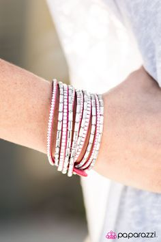 A band of pink suede is spliced into six glistening strands and decorated with white rhinestones, glassy emerald-cut gems, and flat silver cube beads. The elongated design allows for a trendy double wrap around the wrist. Features an adjustable snap closure.   Sold as one individual bracelet.