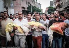 Relatives carry the the bodies of children during the funeral of eight members of the Abu ...