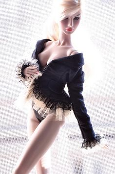 Incredibly well designed image of a BJD of a pretty blonde woman in frilly black and pink lingerie.