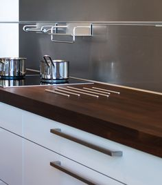A kitchen in Copenhagen's HTH showroom shows interesting details such as stainless steel rods installed in a wood countertop as a heat protector. A useful railing and stainless backsplash adds function.