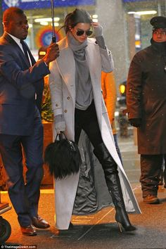 These boots are made for... talking: Kendall Jenner showed off her sexy kinky boots when stepping out in New York City on Friday evening; also with her was a Diddy-style umbrella handler to keep the snow off her famous shoulders