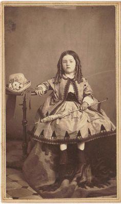 Child wearing civil war era fashions: dress, jacket, umbrella, boots, and hat.