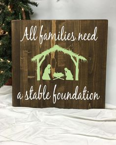 "This beautiful wood sign offers a simple nativity scene and the quote All Families Need a Stable Foundation. The board features two colors of vinyl to add dimension and to put focus on each aspect of the vinyl design. This sign is pine & measures 18"" w x 18"" h x 3/4 thick. Vinyl letters. Flowers not included. Handmade in the USA. We always strive for great customer service. If you have a question or concern about one of our products please don't hesitate to contact us and we will handle it…"