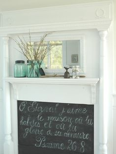 In love with this idea! Faux fireplace with a chalkboard background. A verse written in french on the chalkboard!