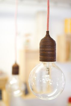 lasercut lamp holder from kirin notebook. love the combo of the wood, the red cord, and the round bulb.