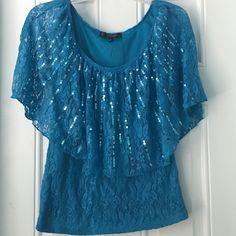 HPCute Sparkly Blue Top This cute sparkly blue top is perfect for many occasions! The top has a floral design and the front has a sparkly look. It is 95% nylon and 8% spandex and the inside lining of the top is 100% polyester. It has been worn once or twice. Let me know if you're interested! HeartSoul Tops Blouses