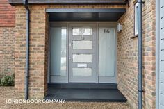 Modern grey front door with multiple glazed panels and full-length opaque sidelights. Finished with contemporary polished chrome door furniture. Front Door Design, Glass Panel Door, House Front, Contemporary Front Doors, Grey Front Doors, Front Door, Front Door Numbers, External House Doors, Modern