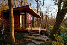 Set in a wooded area, this 300-square-foot studio retreat in Chappaqua, New York, is nestled between two rock outcroppings — one is used as a backdrop and the other as a bookend to the deck. The design team at Workshop/apd chose Dark Ipe siding and decking and walnut interiors for a natural mid-century modern look that connects the structure to its wooded surroundings.