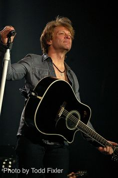 "Jon Bon Jovi - Looking out at the audience while holding his fav guitar. That guitar has ""A.P."" etched in it (the initials of Jon's guitar teacher/mentor), and ""1994"" - the year ""A.P."" died."