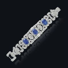 AN ART DECO SAPPHIRE AND DIAMOND BRACELET -  The pavé-set diamond openwork band decorated with baguette-cut diamond fan motifs and enhanced with three cushion-shaped sapphires, mounted in platinum, 1930s