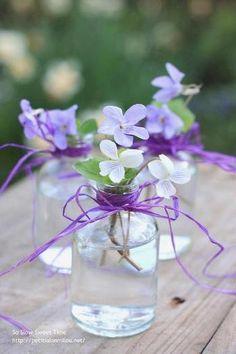 庭で見つけたスミレの花を摘んで細口びんに挿すだけのナチュラルなしつらえ。口元にラフィアでおめかしすると、キュートなブーケのようです。