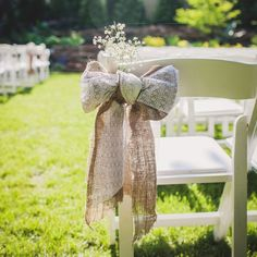 Bows of lace and burlap accented with baby's breath to mark the aisles of an outdoor wedding ceremony.
