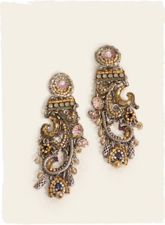 The handcrafted earrings are scrolled with elaborate metallic and glass beadwork.