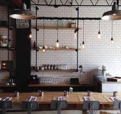 superbe exemple de cuisine industrielle, mur carrelage blanc, table en bois et chaises industrielles en métal, jolies etageres industrielles