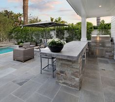 Outdoor Kitchen. The outdoor kitchen features concrete countertop and stone. These pavers are a natural stone called Shadow Gray. Outdoor Kitchen Outdoor Kitchen Ideas. Outdoor Kitchen Layout #OutdoorKitchen Brandon Architects, Inc