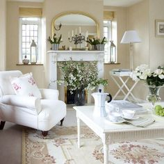 beautiful white cottage living room, area rug, fireplace, floral arrangements, mirror <3