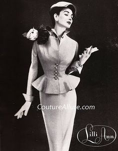 From 1955, this ensemble consists of an empire waisted sheath dress and matching peplum jacket.