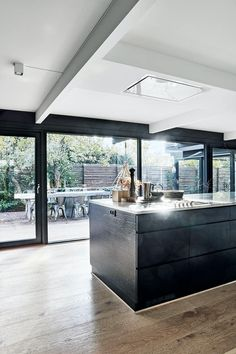 The spacious kitchen seems even larger with the big windows. Big Windows, House Windows, Modern American Kitchens, Cozy Kitchen, Kitchen Island, Kitchen Models, Fritz Hansen, Kitchen Styling, Home Fashion