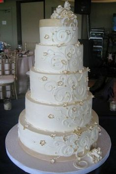 This fabulous wedding cake was buttercream adorned with fondant ribbon in antique gold, white fondant scrolls, gold-edged sugar blossoms, and sugarpaste ruffles at the top and base.