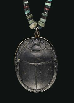 AN EGYPTIAN GREEN SCHIST SCARAB LATE PERIOD TO PTOLEMAIC PERIOD, 664-30 B.C. The details of the beetle well articulated, the underside unengraved, mounted in a modern gold frame, strung as a pendant in a necklace composed of green, gray, red, yellow, and black faience disk beads 21¼ in. (54 cm.) long