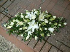 Serene all white small casket spray